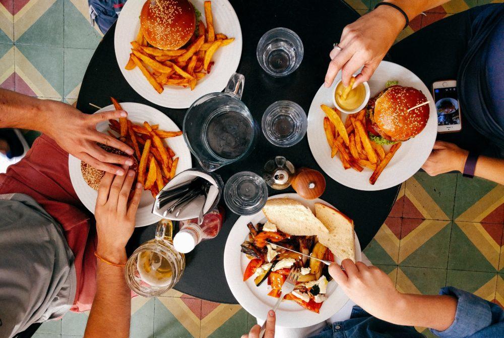 レストランでハンバーガーやサラダを食べる4人の友達