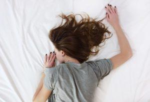 疲れ果ててベッドに横たわる少女