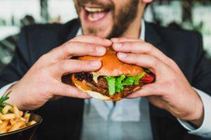 代替肉のヴィーガンバーガーを食べる男性